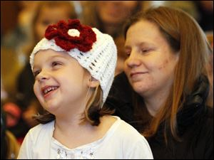 Grace Korte, 5, sits on her mother Alison Korte's lap while enjoying a puppet show.
