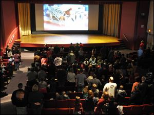 "Some 250 people stand for the playing of the national anthem ahead of a showing of ""Hotel Transylvania"" inside the theater at South Dakota's Ellsworth Air Force Base on its last day of operation, Saturday."