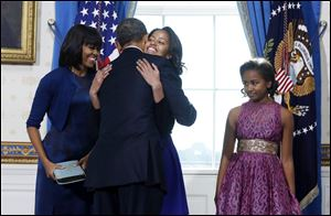 President Obama hugs daughter Malia as the First Lady and daughter Sasha look on. Sasha told her father 'good job,' after the oath was completed.