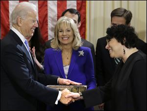 Vice President Joe Biden, with his wife, Jill Biden, center, holding the family Bible, shakes hands with Justice Sonia Sotomayor after taking his oath of office.