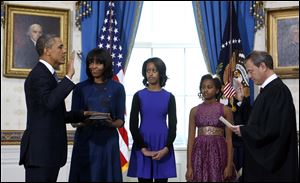 President Barack Obama is officially sworn-in by Chief Justice John Roberts in the Blue Room of the White House during the 57th Presidential Inauguration today. Next to Obama are first lady Michelle Obama, holding the Robinson Family Bible, and daughters Malia and Sasha.