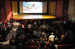 Some 250 people stand for the playing of the national anthem ahead of a showing of
