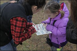 Kate Zimmerman and Grace Korte, 5, work together to identify a bird.