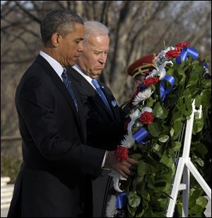President Obama and Vice President Joe Biden place a wreath at the Tomb of the Unknowns on Sunday at Arlington National Cemetery in Arlington, Va.