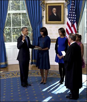President Obama is sworn in with the family Bible held by First Lady Michelle Obama, as daughters Malia and Sasha watch in the Blue Room of the White House. Supreme Court Chief Justice John Roberts administered the oath on Sunday.