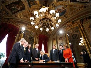 President Barack Obama, surrounded by Congressional leaders, signs a proclamation to commemorate the inauguration, entitled a National Day of Hope and Resolve, following his ceremonial swearing-in ceremony. From left are, Senate Majority Leader Harry Reid of Nev., Sen. Lamar Alexander, R-Tenn., Sen. Charles Schumer, D-N.Y., Vice President Joe Biden, House Speaker John Boehner of Ohio, House Majority Leader Eric Cantor of Va., and House Minority Leader Nancy Pelosi of Calif. (AP Photo/Jonathan Ernst, Pool)