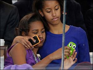 Malia Obama, right, and Sasha Obama look on from the presidential box during the Inaugural parade.