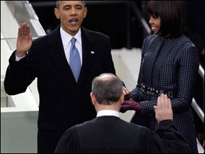 President Barack Obama receives the oath of office from Chief Justice John Roberts as first Lady Michelle holds the bible at the ceremonial swearing-in.