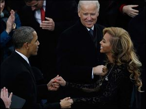 Vice President Joe Biden, right, watches as President Barack Obama greets Beyonce.