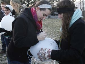 From left, Julia Debelly and Shayna Zack write a joint message to Morgan on their balloon.