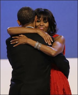 First lady Michelle Obama wraps her arms around President Barack Obama while dancing during the Inaugural Ball at the 57th Presidential Inauguration.