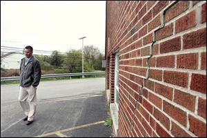 Pat Murtha, Rossford High School vice-principal, walks by cracks in the wall of Rossford High School, which was built in 1922. Bringing the high school up to standards would cost $18 million over 10 years.