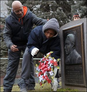 Frankie West, left, watches Amadeus Cannon, right, lay a wreath today at a memorial during the Martin Luther King Civil Rights Movement March at Martin Luther King Park in Bethlehem, Pa.