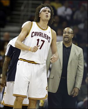 Cleveland Cavaliers' Anderson Varejao (17), from Brazil, grimaces after hitting the floor during an NBA basketball game against the Toronto Raptors in Cleveland.