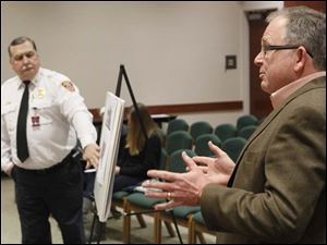 Sylvania Township fire chief Jeff Kowalski, listens as architect Joseph Vetter, right, fields questions.