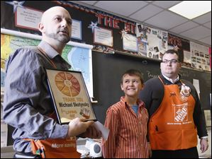 Home Depot's Keith Young, left, and John Smith present Perrysburg Jr. High School student Michael Skotynsky with a plaque.