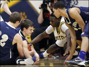 St. John's Jesuit's Trevor Walsh (22) and Austin Gardner (10) battle Whitmer's Jon Ashe (22) for  a loose ball.