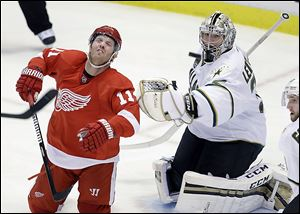 The Red Wings' Daniel Cleary, left, reacts after getting hit with the puck in front
