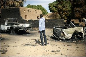 An unidentified man takes a picture of  the charred remains of trucks used by radical Islamists on the outskirt of Diabaly, Mali,  some  460kms (320 miles) North of the capital Bamako, Monday.