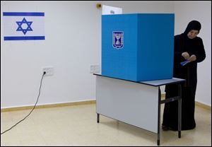 An Arab Israeli woman casts her vote during legislative elections today in the town of Tira, central Israel.
