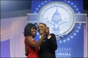 President Barack Obama and first lady Michelle Obama, wearing a ruby colored chiffon and velvet Jason Wu gown, dance.