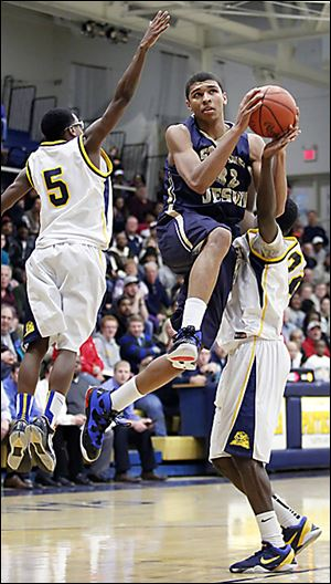 Whitmer's Jon Ashe, right, tries to thwart St. John's Marc Loving's trip to the basket while Chris Parker (5) attempts a block in Tuesday's contest in the Whitmer Fieldhouse. The visiting Titans won 52-51.