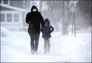 David Range walks his daughter Abigail Range, 10, to Perry Elementary in Erie, Pa. The freezing tempera-tures caused icy roads across much of the state.