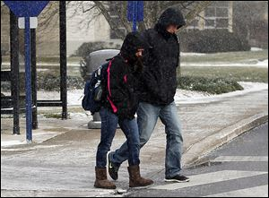 Sophomores Taylor Juza, left, and Kyle Mauter are bundled up against single-digit temperatures as they cross the University of Toledo campus on Tuesday.