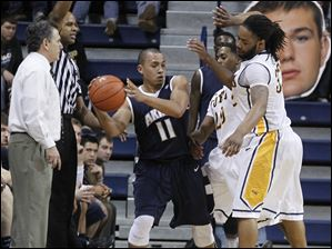 Akron's Alex Abreu is boxed in by UT's Julius Brown, center, and Reese Holliday.