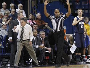 A referee signals a 3-pointer by Akron's Chauncey Gilliam. Akron head coach at left is Keith Dambrot.