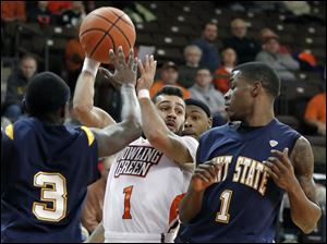 Bowling Green State University guard Jordon Crawford looks for an opening against Kent State guard Randal Holt (3) and guard Kris Brewer (1).