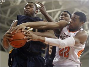 Bowling Green State University forward Richaun Holmes (22) battles Kent State forward Khaliq Spicer (21) and forward Chris Evans (5) for a rebound.