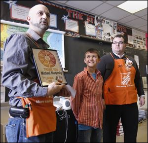 Home Depot's Keith Young, left, and John Smith give Perrysburg Junior High School student Michael Skotynsky a plaque for writing to the store, requesting assistance for Cherry Street Mission.