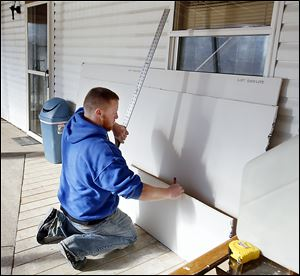 Volunteer Brandon Reynolds helps with drywall at You Lucky Dog in Oregon. Insurance helped pay for some of the damage caused by the storm, but not all.