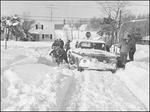 Everyone gives a hand to dig out this Rossway car stuck in the snow following the Blizzard of 1978.