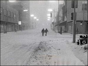 People walk east on Adams Street approaching Huron Street during the Blizzard of 1978.