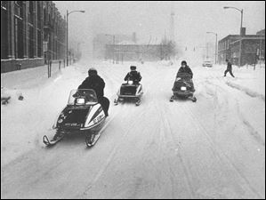 Snowmobiles driven by  Carl Beach and his sons Randy and Chris head out to help those in trouble in Michigan during the blizzard.