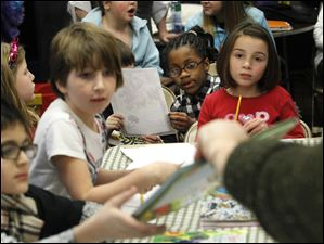 Tatiyana Esmond, 6, center, looks at a book being passed around Thursday evening.