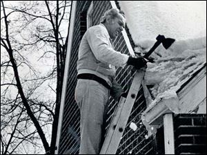 Don Dankert of  Boydson Drive uses a hand axe to clear ice on his roof after the blizzard.