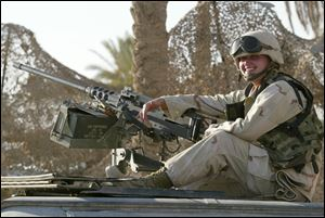 Aneta Urban sitting with a .50-cal. machine gun atop a Humvee in September 2003 while she was serving in the U.S. Marines with a military police company in Iraq.