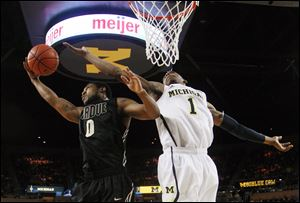 Purdue guard Terone Johnson grabs a rebound against Michigan forward Glenn Robinson III during the first half Thursday.