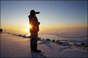 ROV frozen25p    Christopher Jenkins enjoys a cup of coffee and the sunrise over Lake Erie as he scans the horizon for wildlife on a frigid morning at Luna Pier, Mi., Thursday, January 24, 2013.  The Blade/Andy Morrison