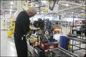 An employee adds an engine's electrical harness at Chrysler's Dundee Engine Plant. Chrysler chose to eliminate one of the plant's shifts after somewhat disappointing sales of the Dodge Dart and Fiat 500.