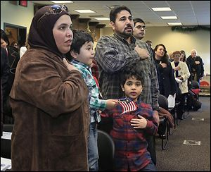 Dalih El-Far, left, her husband, Mohamed, hand on heart, and two of their children, Hashim, 3, and Ahmed, 6, say the Pledge of Allegiance during Thursday's naturalization ceremony.