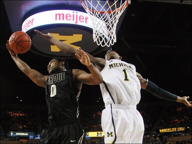 Purdue Michigan Basketball Purdue guard Terone Johnson grabs a rebound against Michigan forward Glenn Robinson III during the first half Thursday.
