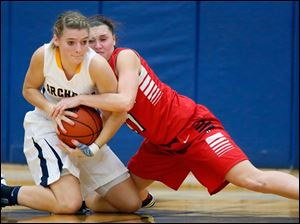 Archbold's Cassidy Wyse (15) battles Wauseon's Alyssa Reed (21) for a loose ball during a basketball game.