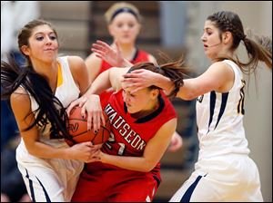 Archbold's Darian Oberlin (21), left, and Winter Fricke (10), right, battle Wauseon's Alyssa Reed (21) the ball during a basketball game.