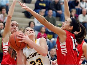 Archbold's Jesse Fidler (23) takes a shot against Wauseon's Haley Archibeque (13) and Sariah Yackee (15) during a basketball game.