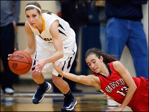 Archbold's Taylor Coressel (14) steals the ball from  Wauseon's Haley Archibeque (13) during a basketball game.