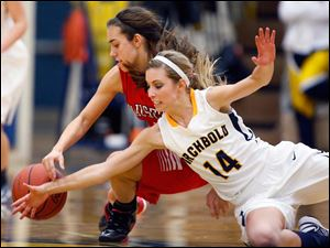 Archbold's Taylor Coressel (14) battles Wauseon's Haley Archibeque (13) for  a loose ball during a basketball game.